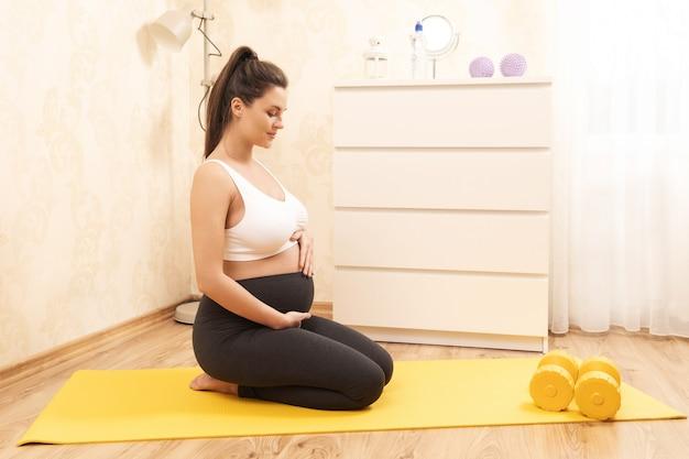 Молодая беременная женщина во время фитнес-тренировки дома