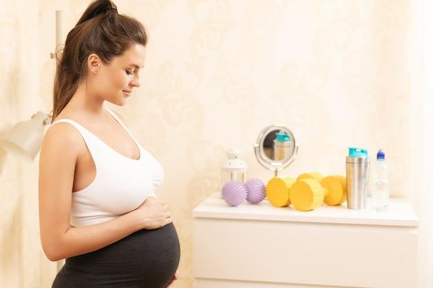 집에서 그녀의 피트 니스 운동을하는 동안 젊은 임산부