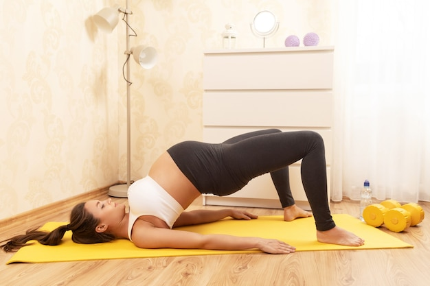 Young pregnant woman during her fitness workout at home