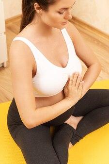 Молодая беременная женщина во время тренировки йоги дома