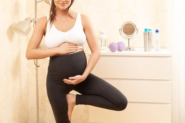 집에서 그녀의 요가 운동을하는 동안 젊은 임산부