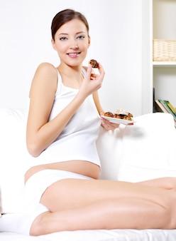 Молодая беременная женщина ест сладкое печенье, сидя на диване у себя дома