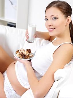 Молодая беременная женщина ест сладкое печенье с молоком дома