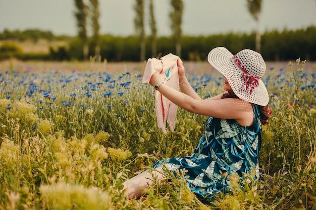 色とりどりの花でいっぱいの野原に座り、ベビー服を持って出産を楽しむ若い妊婦
