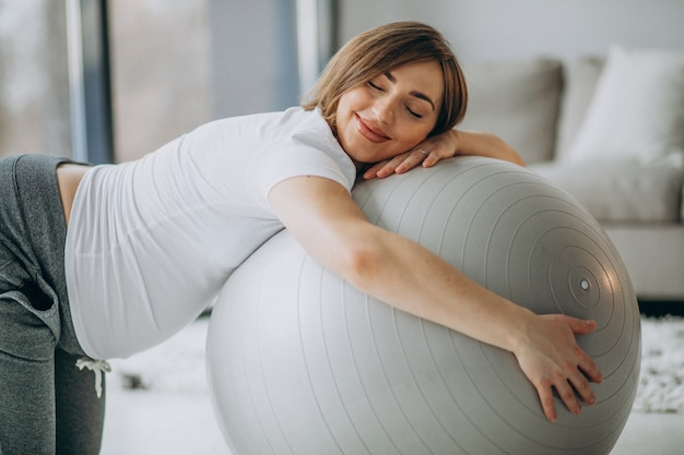 Young pregnant woman exercising yoga with fit ball at home