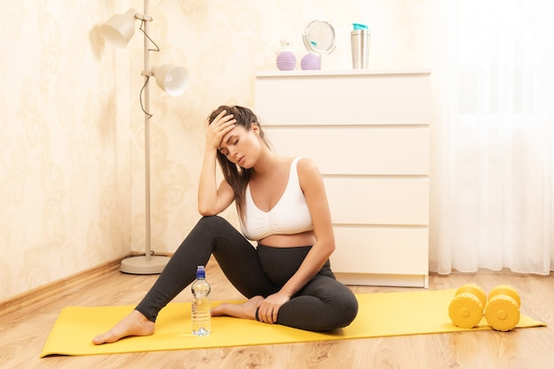 若い妊婦は自宅でのフィットネストレーニング中に気分が悪い