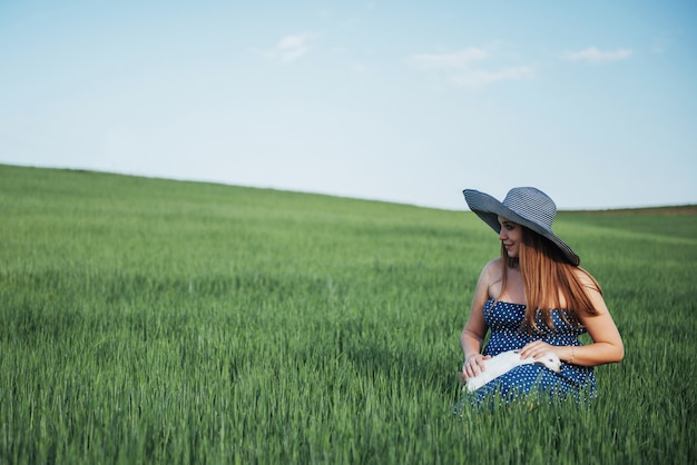 Young pregnant woman in a field of wheat