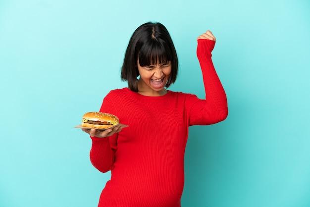 Молодая беременная женщина, держащая гамбургер на изолированном фоне, празднует победу