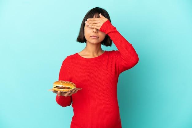 손으로 눈을 덮고 고립 된 배경 위에 햄버거를 들고 젊은 임산부. 뭔가 보고 싶지 않아