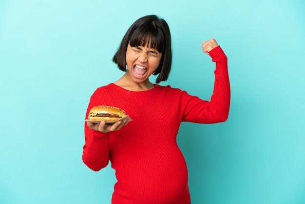 Молодая беременная женщина, держащая гамбургер на изолированном фоне, делает сильный жест