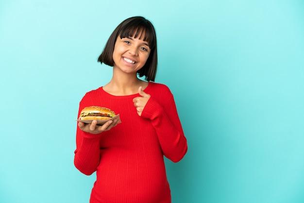 Молодая беременная женщина, держащая гамбургер на изолированном фоне, показывает палец вверх