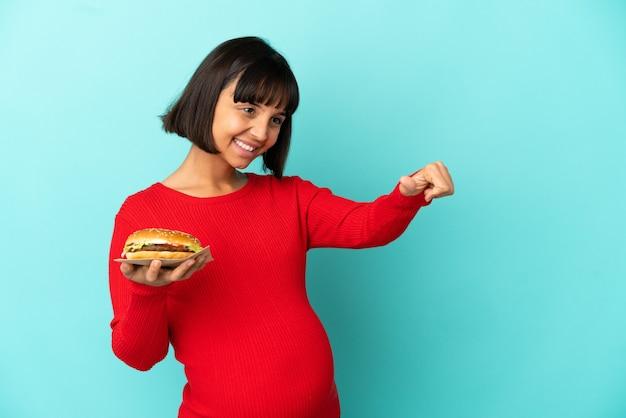 고립된 배경 위에 햄버거를 들고 엄지손가락을 치켜드는 젊은 임산부