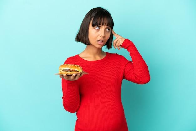 Молодая беременная женщина, держащая гамбургер на изолированном фоне, сомневаясь и думая