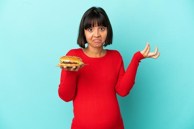 Молодая беременная женщина, держащая гамбургер на изолированном фоне, сомневаясь, поднимая руки