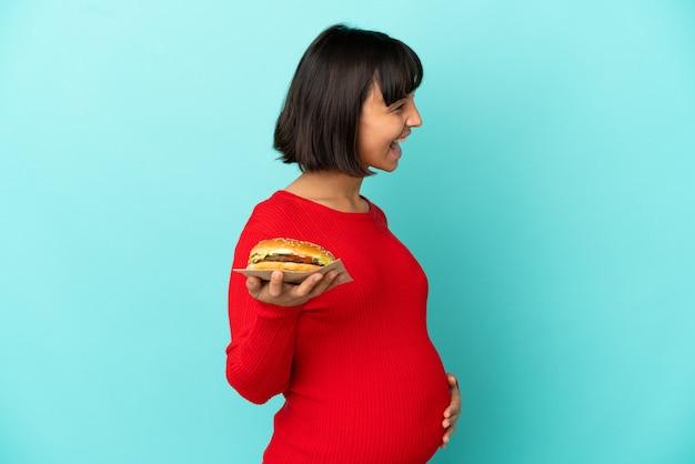 Молодая беременная женщина, держащая гамбургер на изолированном фоне, смеясь в боковом положении