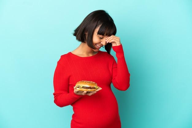 Молодая беременная женщина, держащая гамбургер на изолированном фоне, смеясь