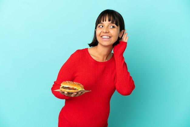 Молодая беременная женщина, держащая гамбургер на изолированном фоне, слушает что-то, положив руку на ухо