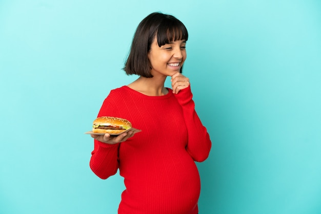 Молодая беременная женщина, держащая гамбургер на изолированном фоне, смотрит в сторону и улыбается