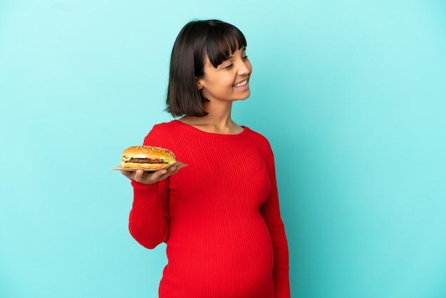외진 배경 위에 햄버거를 들고 옆을 바라보며 웃고 있는 젊은 임산부