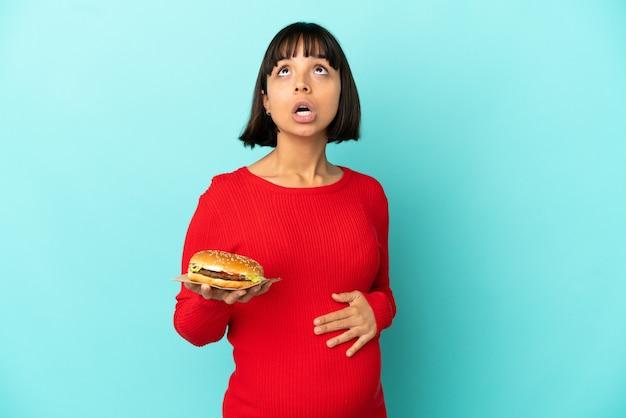Молодая беременная женщина, держащая гамбургер на изолированном фоне, смотрит вверх и с удивленным выражением лица