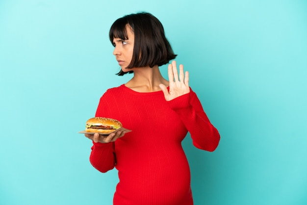 고립된 배경 위에 햄버거를 들고 있는 젊은 임산부가 정지 제스처를 취하고 실망했다