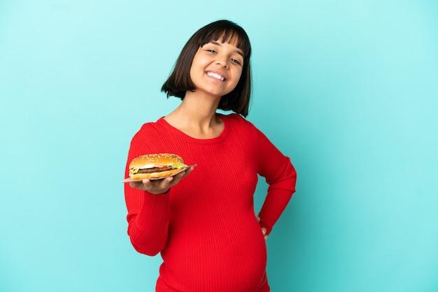 고립된 배경 위에 햄버거를 들고 엉덩이에 팔을 대고 웃고 있는 젊은 임산부