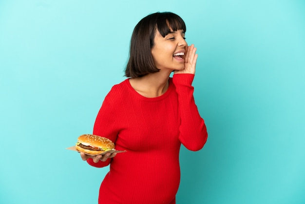 横に大きく開いた口で叫んで孤立した背景の上にハンバーガーを保持している若い妊婦
