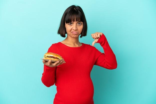 부정적인 표정으로 엄지손가락을 아래로 보여주는 고립 된 배경 위에 햄버거를 들고 젊은 임산부