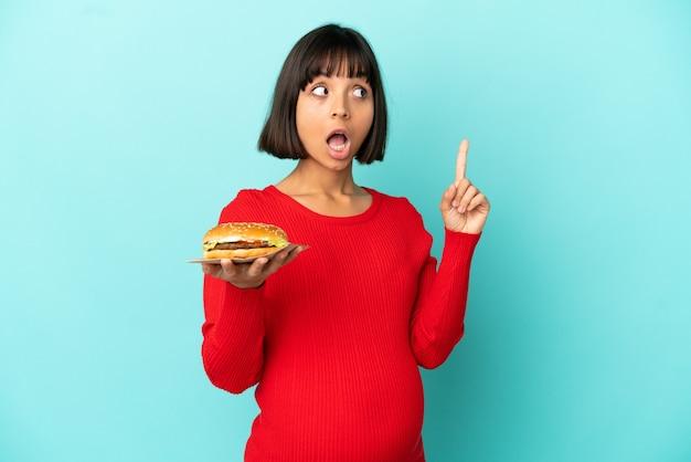 Молодая беременная женщина, держащая гамбургер на изолированном фоне, думает об идее, указывая пальцем вверх