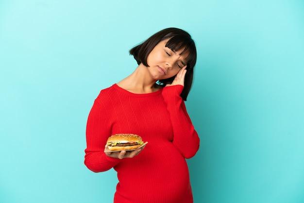 Молодая беременная женщина, держащая гамбургер на изолированном фоне с головной болью
