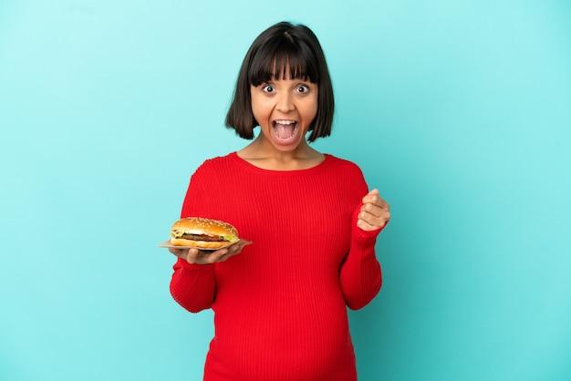 Молодая беременная женщина, держащая гамбургер над изолированной стеной, празднует победу в позиции победителя