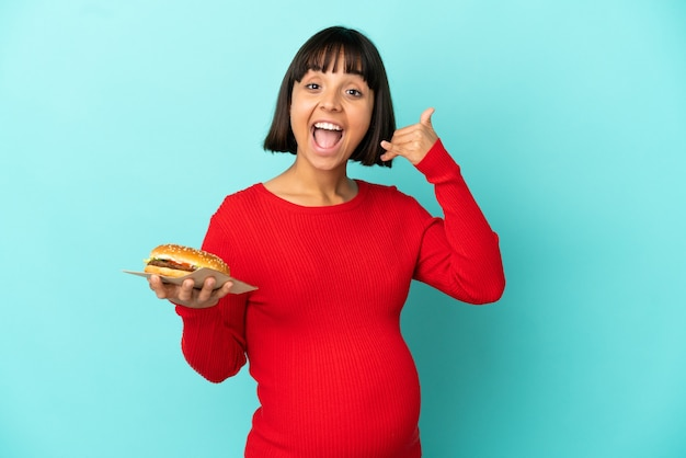 Молодая беременная женщина, держащая гамбургер над изолированной стеной, делая жест по телефону