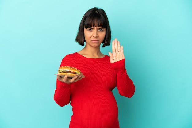 Молодая беременная женщина, держащая гамбургер над изолированной стеной, делая жест стоп