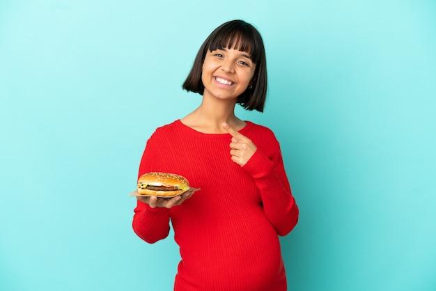 Молодая беременная женщина держит бургер над изолированной стеной, указывая в сторону, чтобы представить продукт