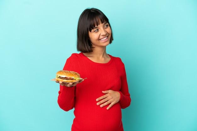 Молодая беременная женщина, держащая гамбургер над изолированной стеной, думая об идее, глядя вверх