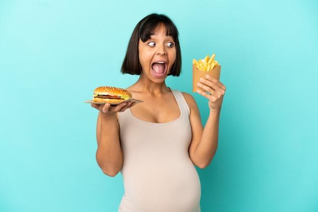 햄버거와 고립 된 파란색 배경 위에 튀긴 된 칩을 들고 젊은 임산부
