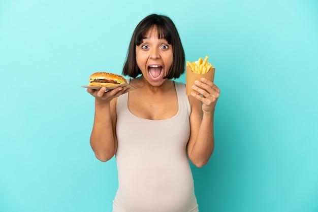 고립 된 파란색 배경 위에 햄버거와 튀긴 칩을 들고 젊은 임산부
