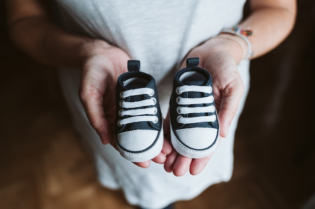Young pregnant woman at home holding baby shoes