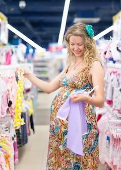 Молодая беременная женщина в детском магазине