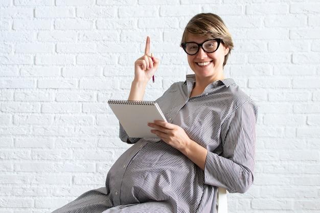Молодая беременная женщина в очках сидит, руки обнимают ее живот