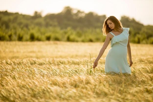 Молодая беременная женщина в поле