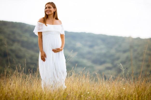 夏のフィールドで白いドレスを着た若い妊婦