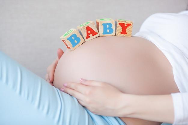 실내 젊은 임신 한 여자. 기대하는 여자의 근접 촬영 초상화입니다. 그녀의 작은 아기 탄생을 기다리는 아름 다운 여성.