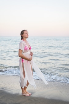 Young pregnant woman is standing on the seashore. hugging her belly and closed eyes. enjoying the moment.