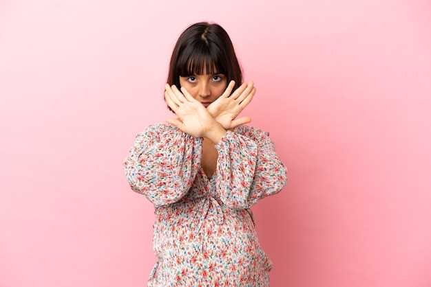 Young pregnant woman over isolated pink background making stop gesture with her hand to stop an act