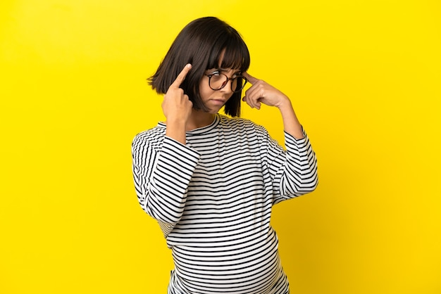 Young pregnant woman over isolated yellow background having doubts and thinking