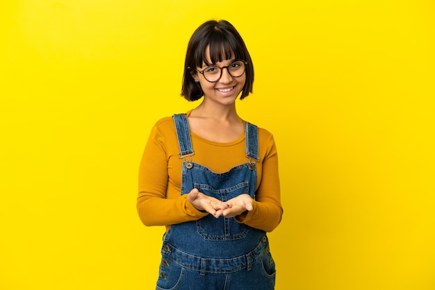 Young pregnant woman over isolated yellow background holding copyspace imaginary on the palm to insert an ad