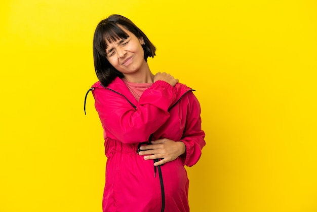 Young pregnant woman over isolated yellow background suffering from pain in shoulder for having made an effort