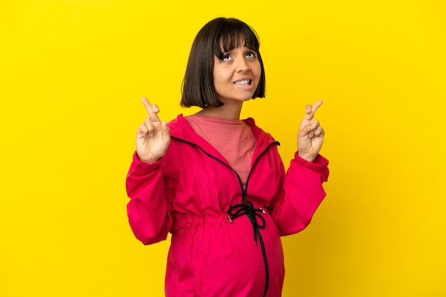 Young pregnant woman over isolated yellow background with fingers crossing and wishing the best