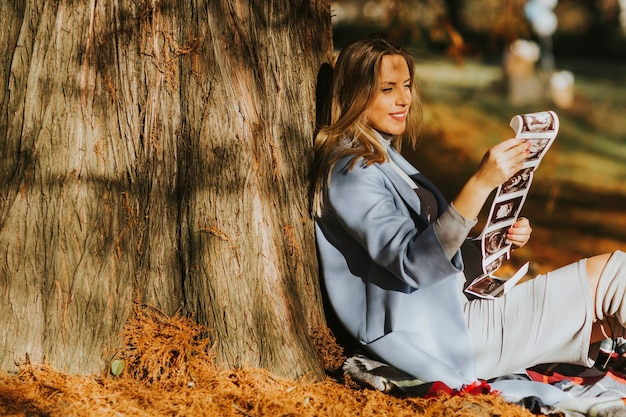Young pregnant woman looking fetus ultrasound images in the park